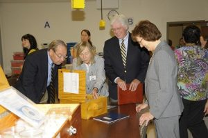"""Above: UTK Chancellor Jimmy Cheek, Tennessee Higher Education Commision Executive Director Dr. Richard Rhoda, and UTK Dean of the College of Arts & Sciences Teresa Lee """"dig in"""" to Biology in a Box's unit on Fossils with Dr. Susan Riechert, Program Director (second from left)."""